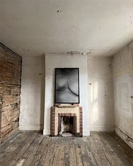 Photograph of a bare room with a fireplace and greyscale photograph of the body