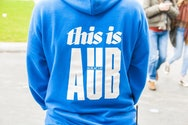 Student Ambassador wearing a blue hoodie which, on the back, reads 'this is AUB' on a Open Day