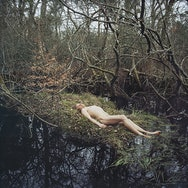 Photograph of naked man lying down in the forest