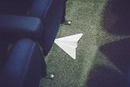 Paper aeroplane underneath a blue sofa