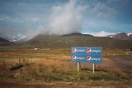 Photograph of Pepsi sign in front of a mountain range