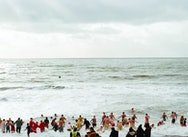 People dressed up as santa running into the sea