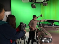 Students working behind the scenes on a film shoot, featuring a green screen.