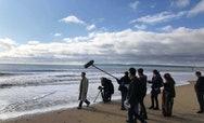 Students filming on the beach