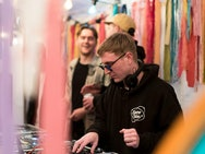 Person wearing sun glasses and a black hooded jumper stands DJing amongst colourful hanging fabric