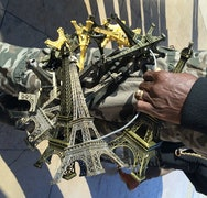A hand holding a ring of different sized Eiffel Tower models