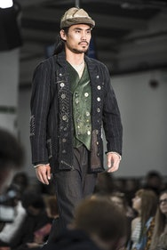 Man on the catwalk with hat and black jacket