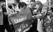 Students holding a poster reading change the world