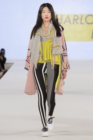 Model wearing yellow top and black and white trousers