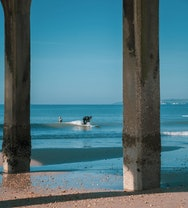 Surfers playing in the sea – they're framed by the pier