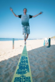 A slack liner playing on the beach