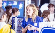 A busy image focussing on a female student ambassador in a blue, AUB branded t-shirt talking to a group of potential students at a careers fair