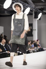Model wearing dungarees and white hat