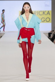 Model wearing light blue top with red trousers