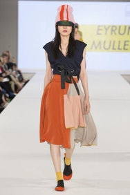 Model wearing black top and orange skirt with riding hat
