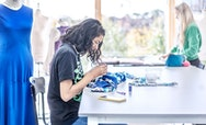 Woman wearing a black t-shirt sat at a desk sewing blue pattered material. There's a blue dress on a mannequin behind her
