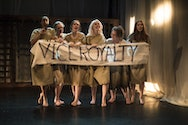Actors on stage holding up a sign saying viceroyalty