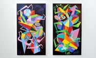 Multicoloured triangular shapes, reminiscent of crystals, painted upon two black canvas hung on a white wall.