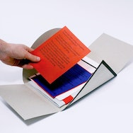 Several loose pieces of printed graphics within a folded case