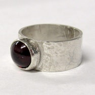 Silver ring with dark ruby coloured stone