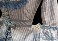 Historical dress made from pale blue and white striped material and blue lace ruffles