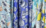 fabric printed with greek-inspired patterns including vases, lemons and octopus