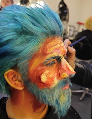 Man wearing orange makeup with blue hair
