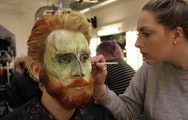 Make-up student painting an Acting student's face for a performance
