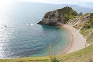 A coved beach on a sunny day, with green, rocky cliffs on the right. The sea is a blue-green and Durdle Door is peaking out behind the cliff.