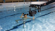 student using filming equipment in water