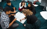 International students sat in a circle on the floor working on a large bit piece of paper