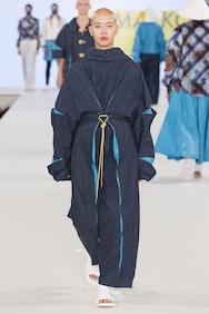 Shaven haired model wearing dark blue coat