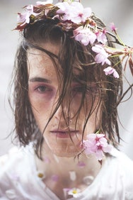 Man with long hair next to flowers