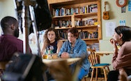 Group of people around a dinning room table being filmed