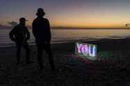 Two men on the beach looking a neon sigh that says 'YOU'