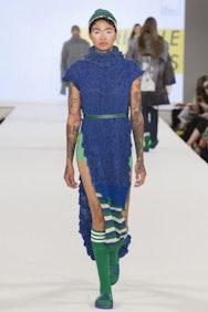 Model wearing blue dress with green belt