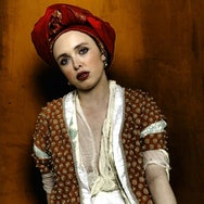 lady in costume with red head piece