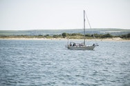 A lone boat bobbing in the sea. In the background is a flat strip of Studland's sandy beach with rolling green hills in the far distance.