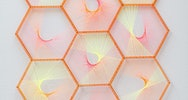 Orange hexagons grouped together like honeycomb with yellow and pink thread laced through