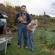 Man and child holding chickens