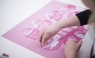 Student using pink paper and pink/white chalk to create abstract artwork