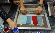 A person doing a screen print with red and blue paints