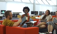 Students sitting in the library and discussing a book