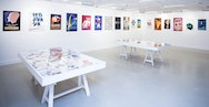 Colourful posters displayed on TheGallery's walls with two tables in the middle of the room.