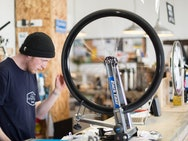man wearing a black knitted hat is inspecting a bicycle wheel in a workshop