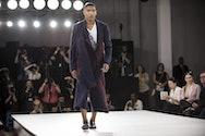 Male model wearing long overcoat on the catwalk