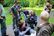 Students operating a camera in a park