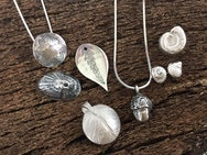 Silver pendant with several earrings