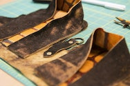 Close up of several pieces of leather on a cutting matt