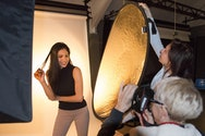 One student taking a photograph of a model, whilst another hold a reflector